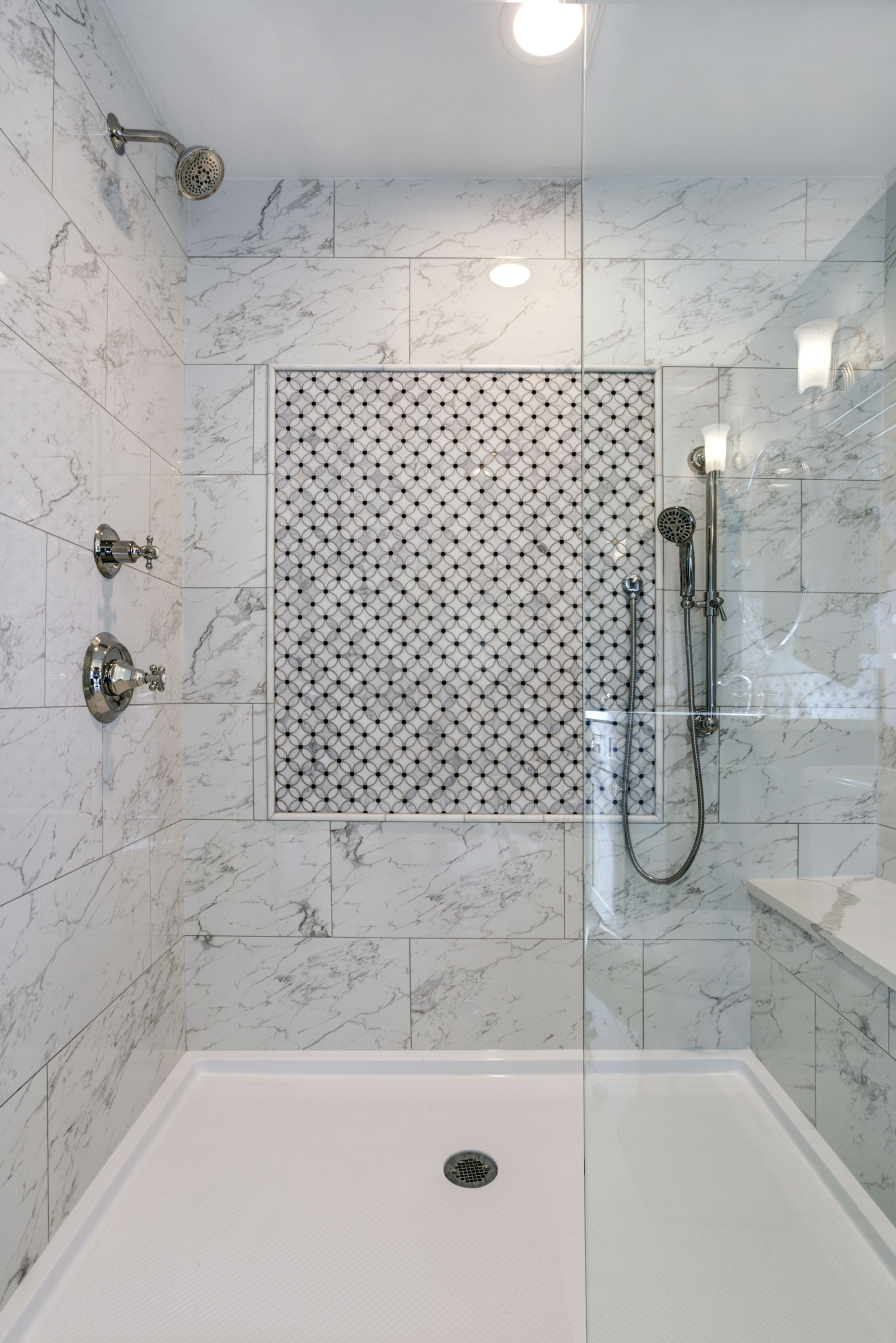 A bathroom shower with tiles on its walls.
