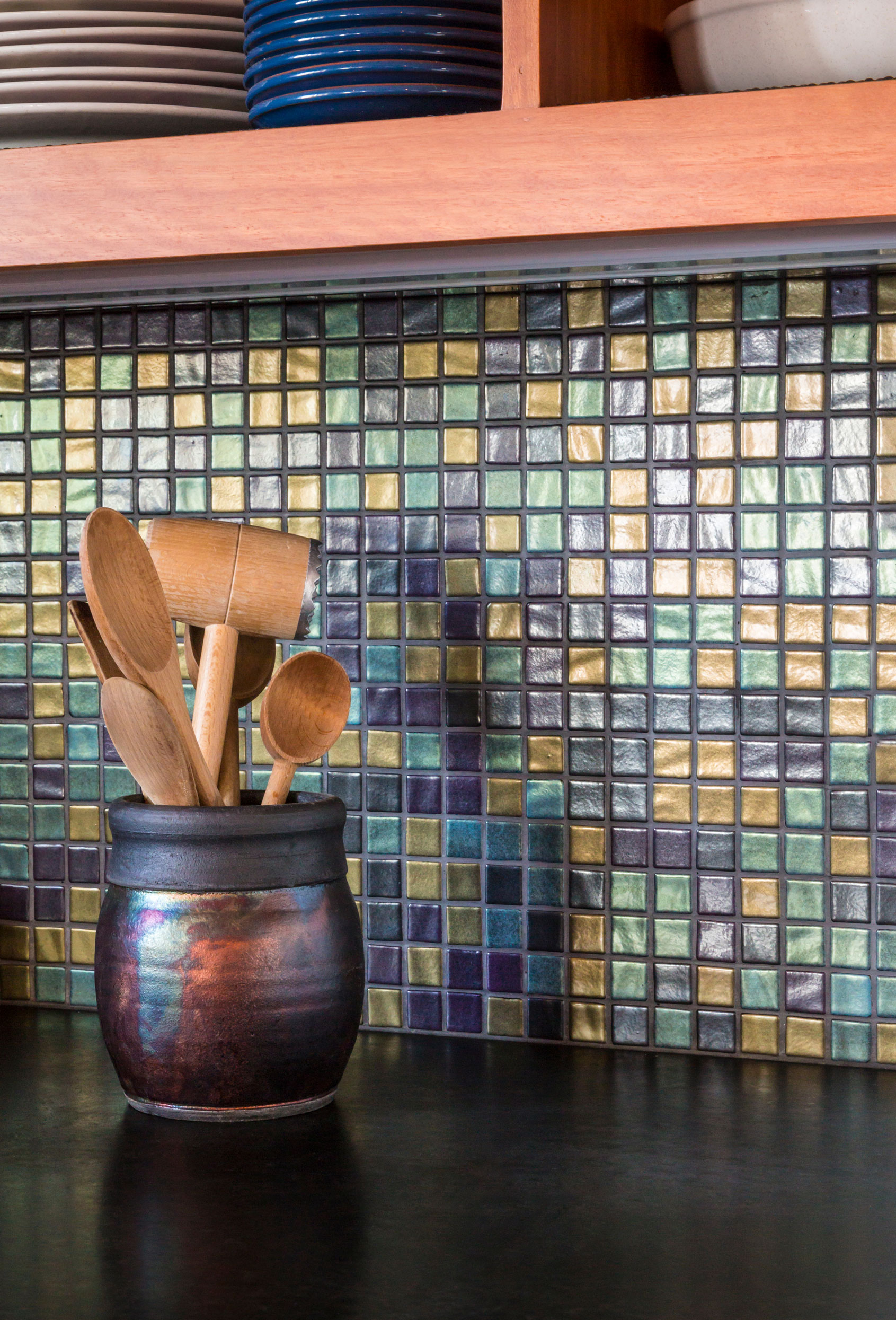 A beautiful kitchen with mosaic tiles on its walls.