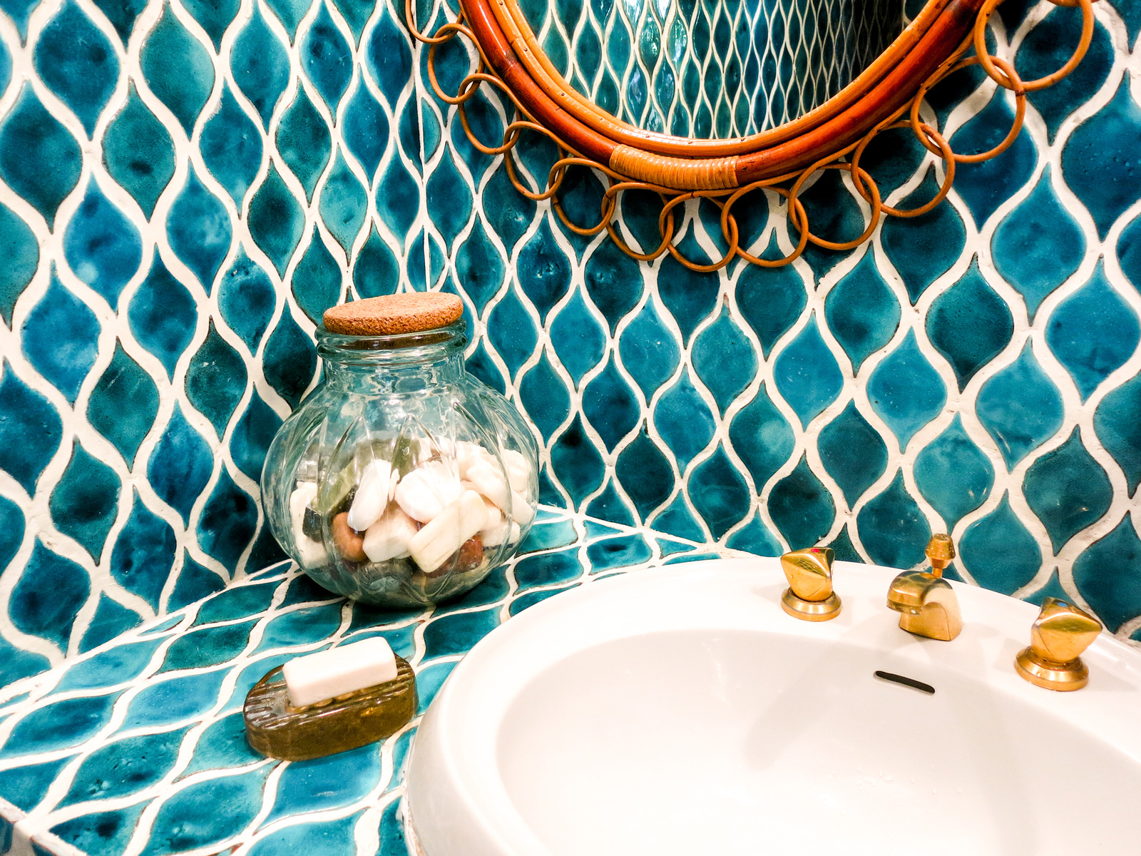 A pretty bathroom counter with a soap dish and a decorative item on it.